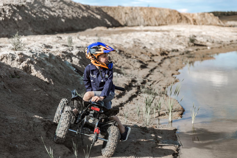 Berniukas su šalmu ant keturračio važiuoja per purvą šalia ežero