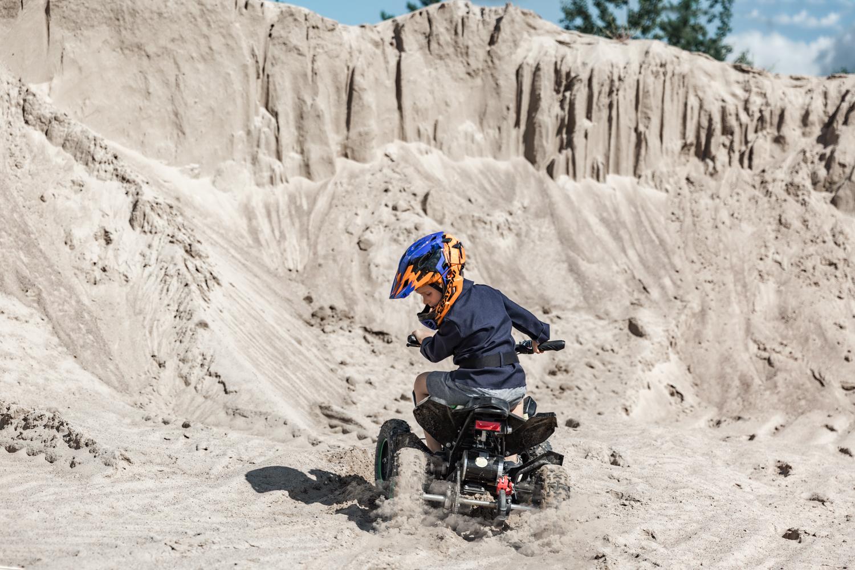 Vaikas su keturračiu važiuoja smėlio karjere per gimtadienio fotosesiją