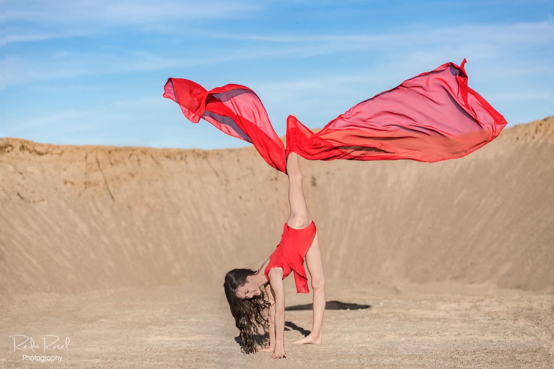 Gimnastė, apsivilkusi raudonu sportinės gimnastikos triko
