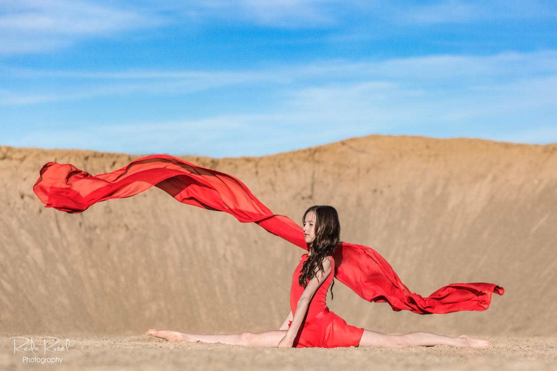 Mergaitė raudonu meninės gimnastikos triko ir raudonu šaliku atlieka špagatą