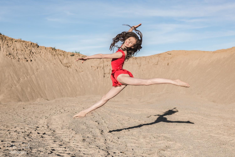 Besišypsanti gimnastė mergaitė smėlio karjere atlieka špagatą ore