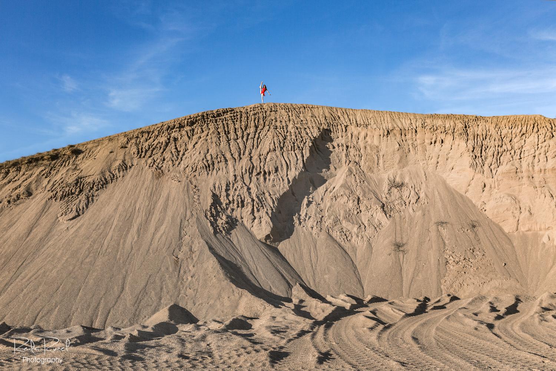 Gimnastės siluetas smėlio karjero ir dangaus fone