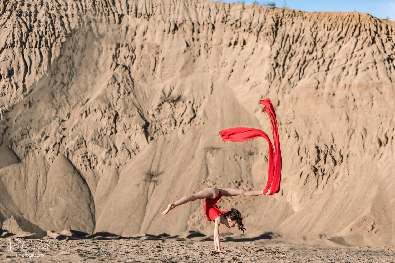 Gimnastė raudonu triko stovi ant rankų, plėvesuoja raudonas šalikėlis