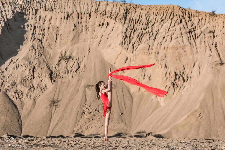Sportininkė raudonu gimnastikos triko atlieka meninės gimnastikos figūrą