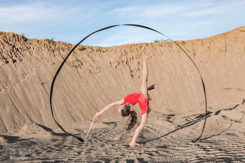 Meninės gimnastikos fotografija, mergaitė raudonu triko su juodu meninės gimnastikos kaspinu