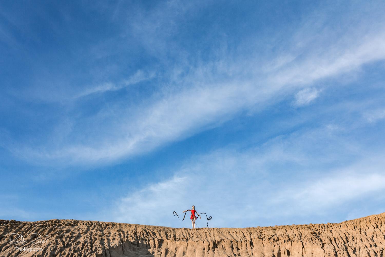 Meninė gimnastika smėlio karjero fone