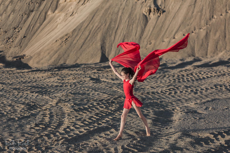 Mergaitė raudona suknele, apsigobusi raudonu šaliu ir ištiesusi rankas žiūri tiesiai