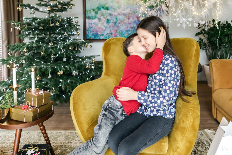 Brolis bučiuoja sesę prie Kalėdinės eglutės