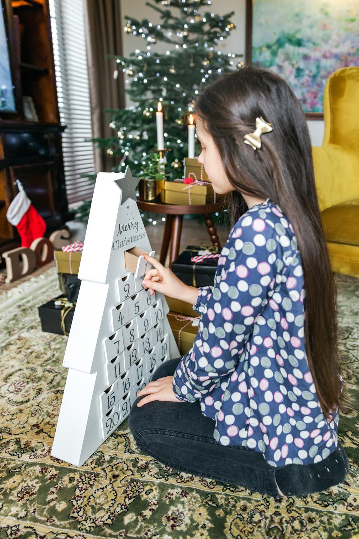 Mergaitė žaidžia su advento mediniu kalendoriumi fotosesijoje